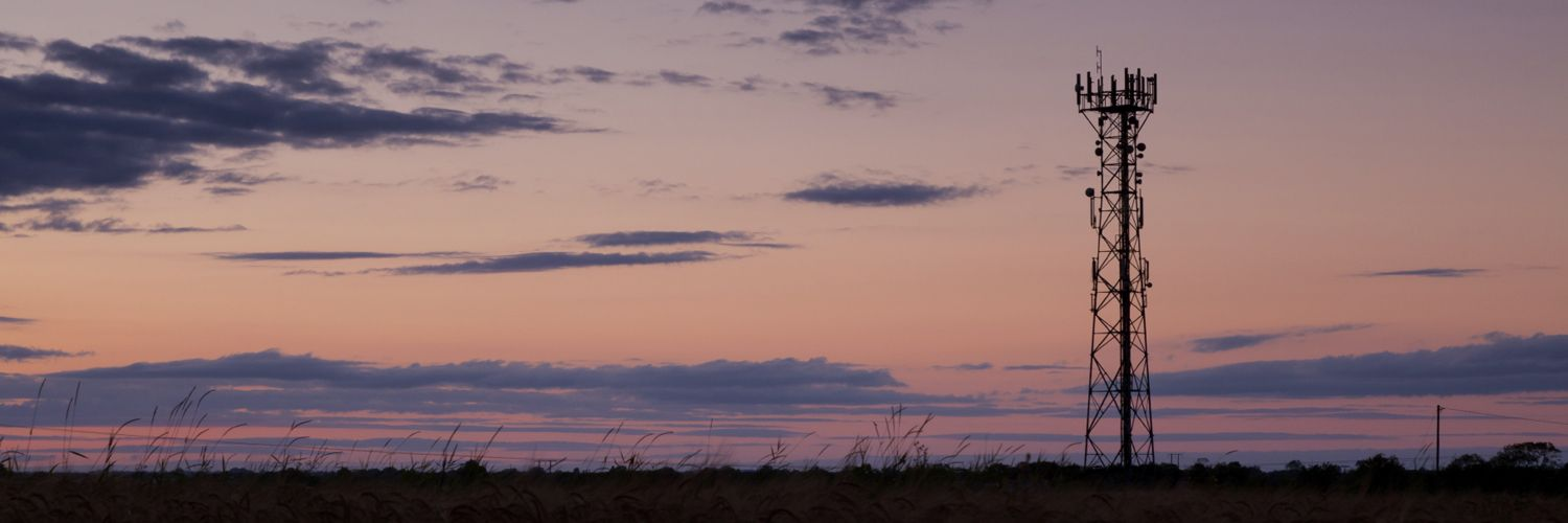 Photograph of cellular network antenna mast against sunset